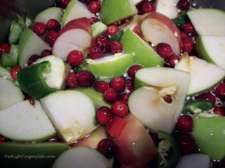 Chopped up apples, green peppers, berries in a stock pot to make Pepper Jelly