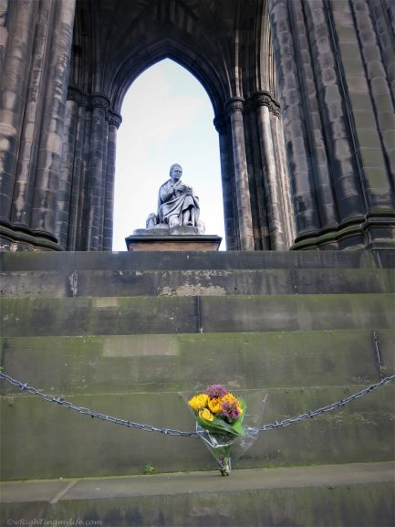Lonely bouquet of yellow and burgundy flowers at base of Scott Monument in Edinburgh Scotland