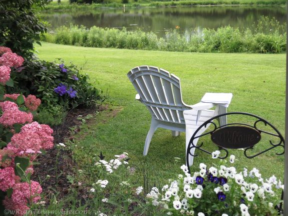 Writing tablet on empty white adirondeck chair amidst pink hydrangea and pot of pansies on green grass overlooking pond