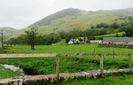 House amidst green pasture and mountain backdrop