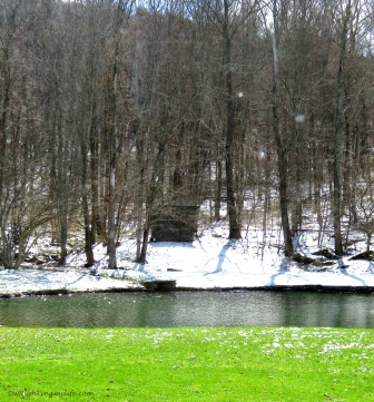 Snow covered hill with green grass and flowing pond in forefront