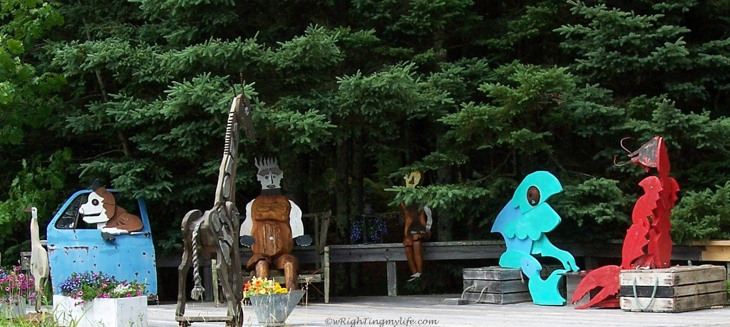 Painted metal sculptures of people and creatures in the woods