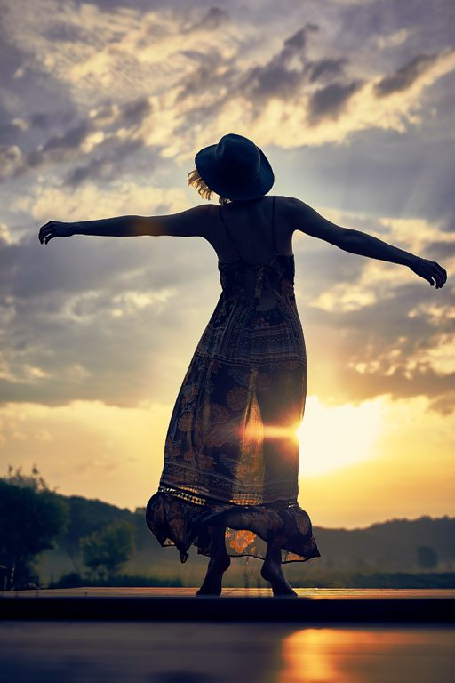 person moving freely with sunshine in background