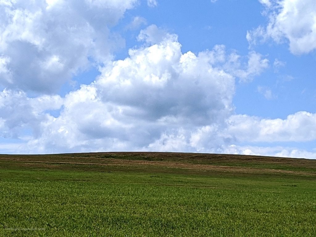 Vivid blue sky and white puffy clouds over green and brown terrain